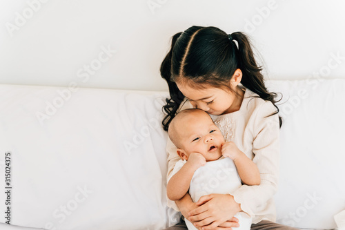 Fototapeta Caring Asian girl in casual wear hugging small brother embracing newborn baby with opened mouth smelling toddler sitting on bed in house obraz