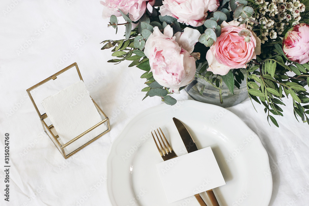 Fototapeta Feminine wedding, birthday mock-up scene. Porcelain plate, blank paper greeting card, golden box and cutlery. Beautiful bouquet of eucalyptus, pink roses and peony flowers. White table background.