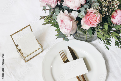 Fototapeta Feminine wedding, birthday mock-up scene. Porcelain plate, blank paper greeting card, golden box and cutlery. Beautiful bouquet of eucalyptus, pink roses and peony flowers. White table background. obraz