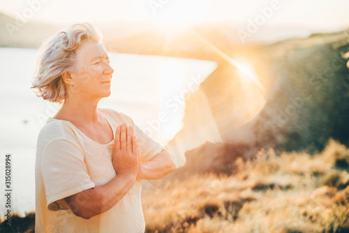 Woman practicing Yoga, meditation close to the sea. She doing different poses on beautiful landscape. Concept of finding yourself and Healthy Life.