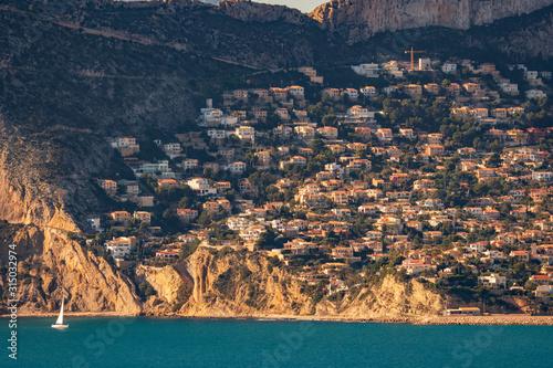 Crowded hillside near sea at sunset, long shot Fototapeta