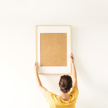 Woman Hold Blank Photo Frame With Empty Copy Space On White Background. Minimal Photographer Artist Concept.