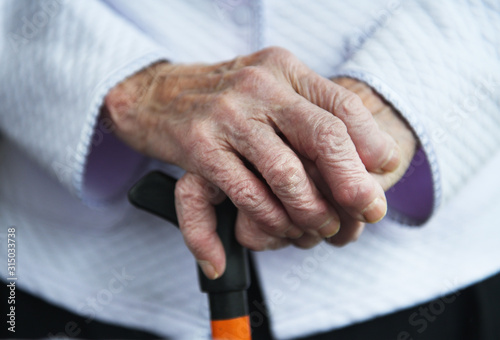 Elderly woman of 90 years put her hands on a cane, retirement and disability, cl Wallpaper Mural