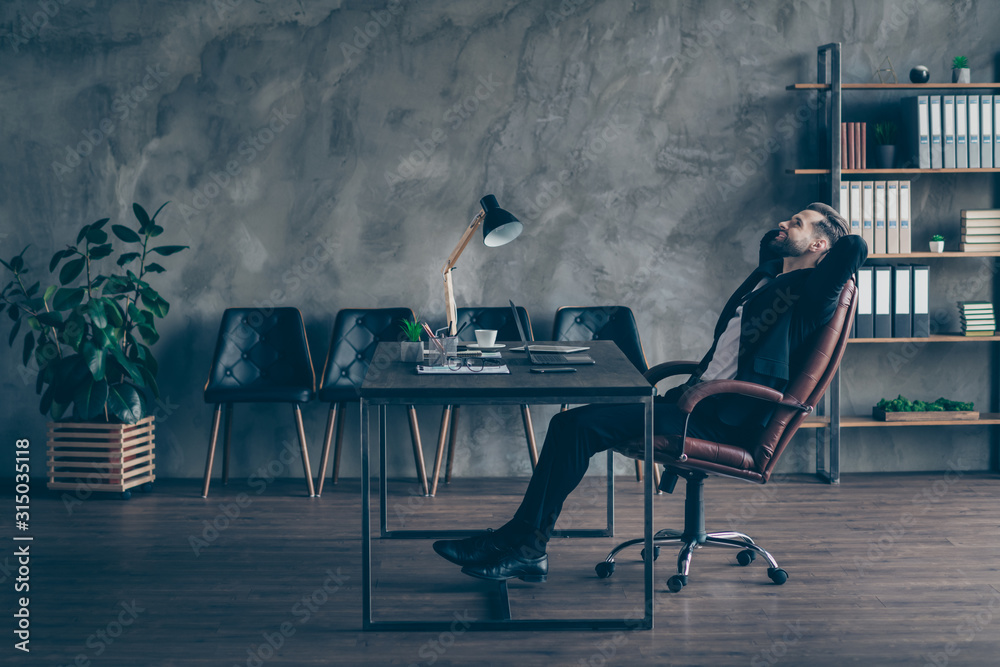 Fototapeta Full body profile photo of handsome chief business guy relaxing toothy smiling hands behind head looking up wear black blazer shirt pants tie suit sit big chair office indoors