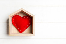 Top View Of Red Textile Heart In A House On Wooden Background. Home Sweet Home Concept. Valentine's Day