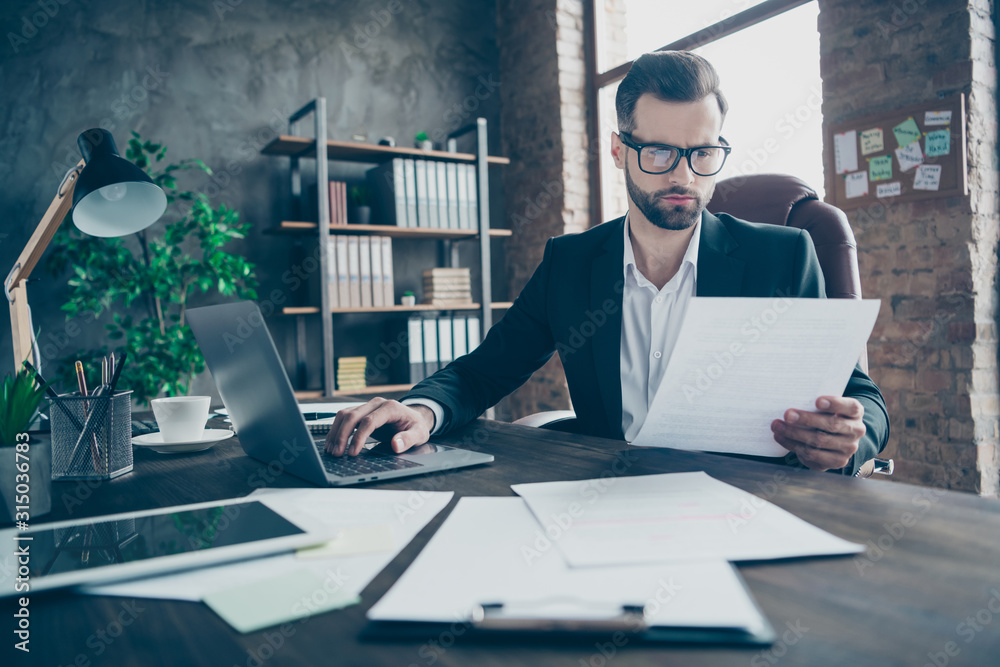 Fototapeta Photo of attentive handsome business brunet guy notebook table reading paper report before filling online statistics wear black blazer white shirt suit sitting chair office indoors