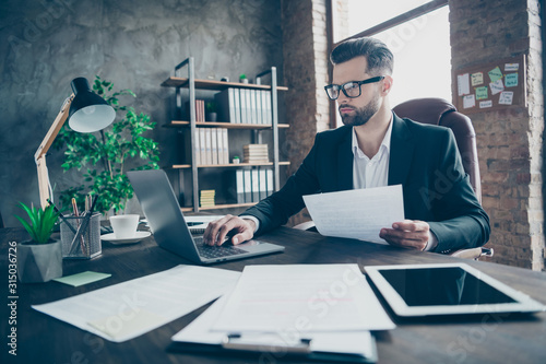 Fotomural  Photo of handsome business brunet guy looking notebook table reading paper repor
