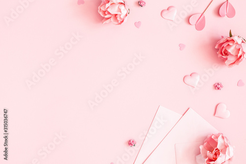 Valentine's Day background. Pink flowers, envelope, hearts on pastel pink background. Valentines day concept. Flat lay, top view, copy space - 315036747