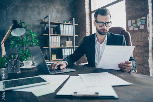 Fototapeta Photo of attentive handsome business brunet guy notebook table reading paper report before filling online statistics wear black blazer white shirt suit sitting chair office indoors obraz