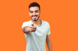 canvas print picture - Hey you! Portrait of cheerful handsome brunette man with beard in white t-shirt pointing finger at camera with joyful toothy smile, choosing you. indoor studio shot isolated on orange background