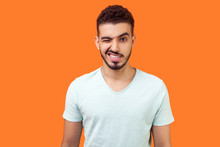 Portrait Of Playful Handsome Brunette Man With Beard In Casual White T-shirt Standing With One Eye Closed, Winking And Flirting At Camera With Grin. Indoor Studio Shot Isolated On Orange Background