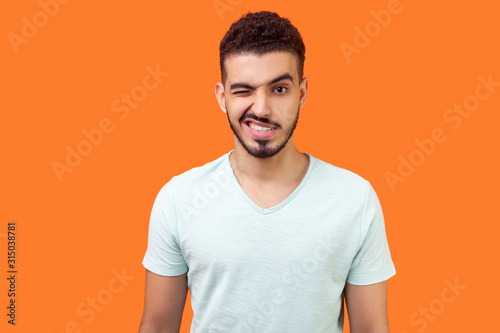 Portrait of playful handsome brunette man with beard in casual white t-shirt standing with one eye closed, winking and flirting at camera with grin Fototapet