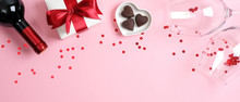 Valentine's Day Banner With Bottle Of Wine Champagne, Gift Box, Two Glasses And Heart Shaped Candies On Pink Background With Confetti. Romance, Love, Valentines Day Romantic Dinner Concept