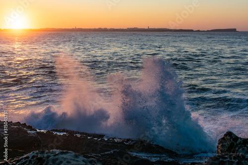 Onda contra as rochas na praia ao por do sol Tapéta, Fotótapéta