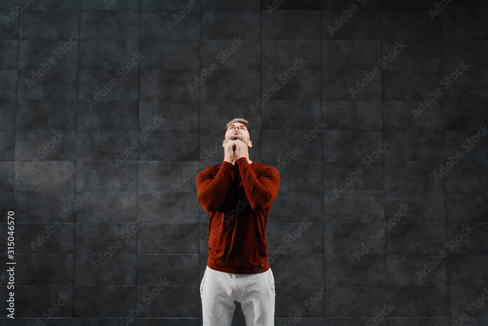 Fototapeta Attractive fit caucasian breaded sportsman in tracksuit doing warm up exercises for neck before running. In background is gray wall.
