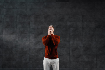 Attractive fit caucasian breaded sportsman in tracksuit doing warm up exercises for neck before running. In background is gray wall.