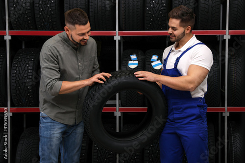 Obraz Mechanic helping client to choose car tire in auto store - fototapety do salonu
