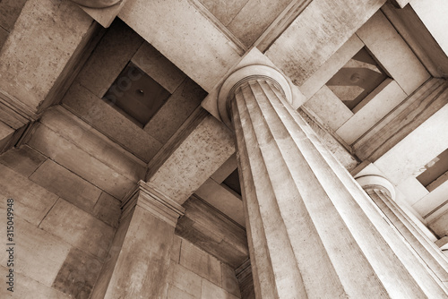Antique stone column of a old building close-up. - fototapety na wymiar