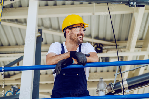 Obraz Smiling handsome caucasian worker in overall and with helmet on head leaning on the railing. Oil production. - fototapety do salonu