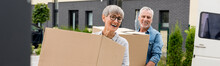 Panoramic Shot Of Mature Man And Smiling Woman Bringing Boxes To New House