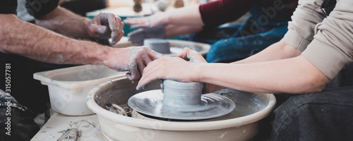 Ceramic crafts workshop master teaching boy how to molding clay pot on pottery wheel