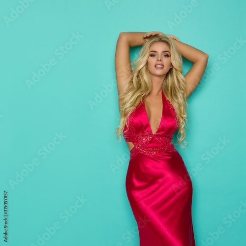 Beautiful Blond Woman In Elegant Red Dress Is Posing With Arms Crossed Behind Her Head Fototapete