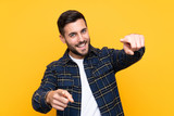 Young handsome man with beard over isolated yellow background points finger at you while smiling