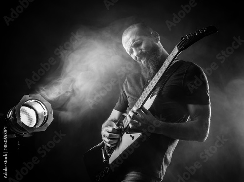 Bearded man playing guitar with spotlight - 315065394