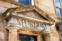 The Museum Sign Above The Entrance Door In Neo Classical Architectural Style