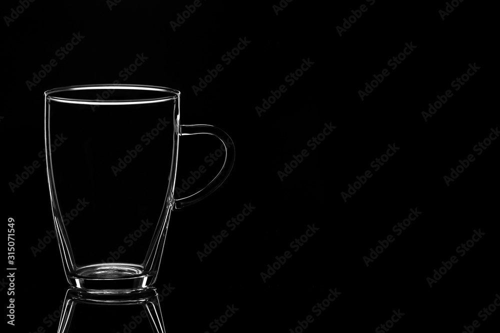 Fototapeta Glass tumbler empty on a black background.