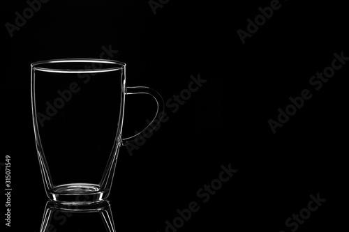 Obraz Glass tumbler empty on a black background. - fototapety do salonu