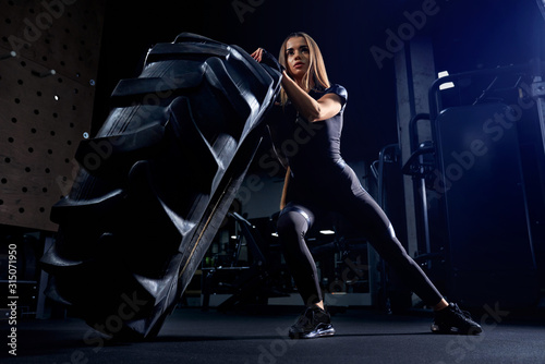 Fotomural Woman pushing giant tire in gym.