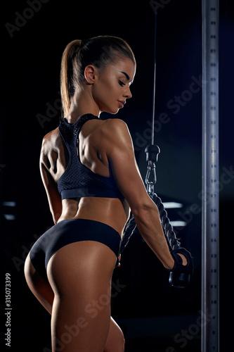Female bodybuilder training triceps in gym.