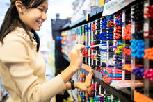 Asian Child Girl Writing Or Experimenting With A Pen On Paper To Buy,color Pens On Pen Shelves In The Shop,teenage Student Is Choosing Different Colors Of Pens In The Stationery Store,office Supplies