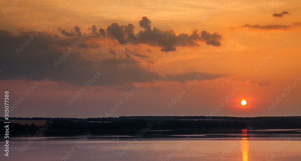 Romantic relaxation evening sunset on the shore of a freshwater lake. Fairytale panorama on the lake with glittering ripples of waves, beautiful colors cloudy evening nature landscape. Forest