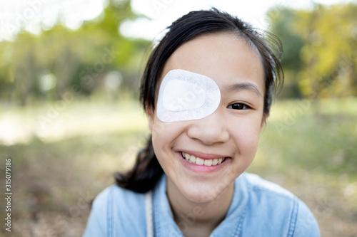 Fototapeta Happy asian child girl cover with blindfolded bandaged eye after surgery or trea
