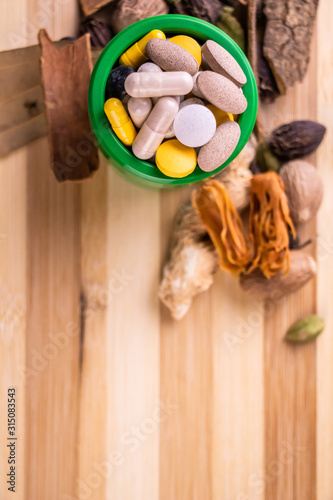 Top view macro shot of herbal pills and tablets arranged with spices on a red stone Wallpaper Mural