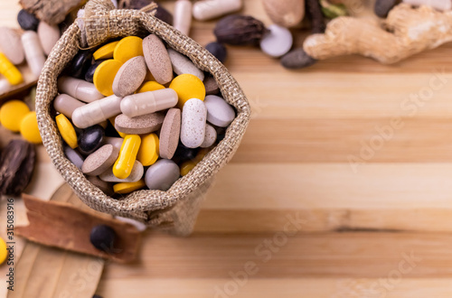 Photo Top view macro shot of herbal pills and tablets arranged with spices on a red stone