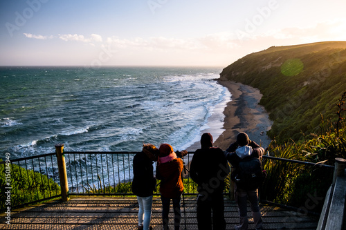 Group of people are looking at the view of the ocean at sunset Wallpaper Mural