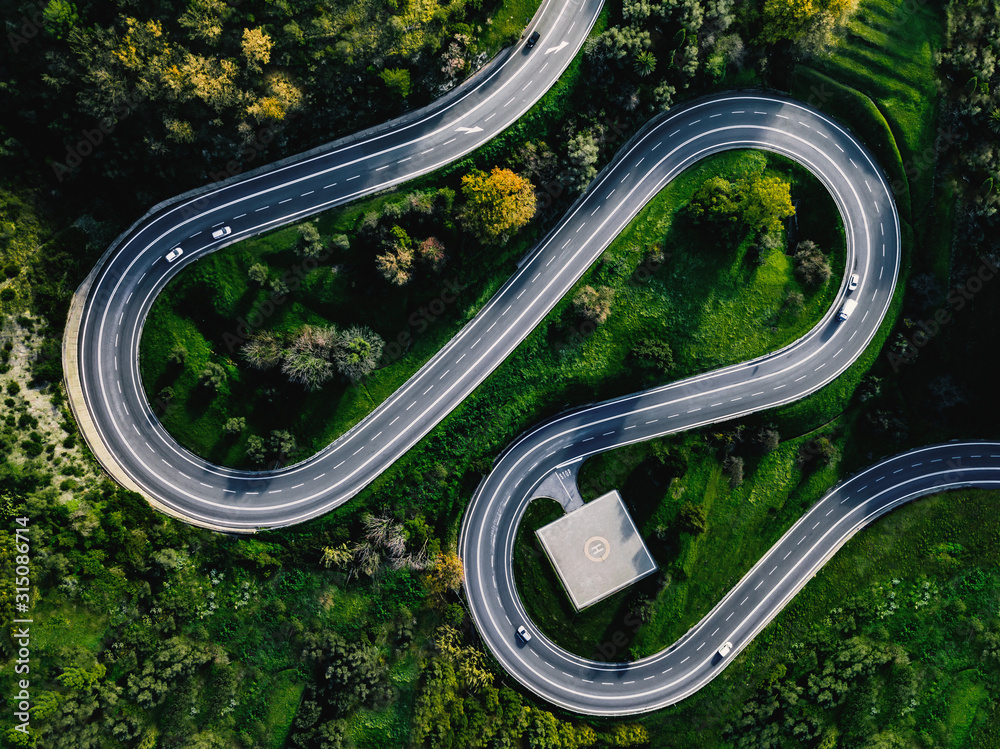 Fototapeta Aerial view of winding curved road with helicopter parking in Italy
