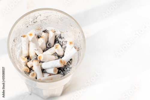 The glass ashtray with dirty cigarettes, white background with copy space Wallpaper Mural