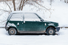 An Old Abandoned Little Green Car Covered With Snow Strewn. Parked On The Edge Of The Woods In Winter
