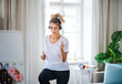 Leinwanddruck Bild - Young woman with headphones doing exercise in bedroom indoors at home.