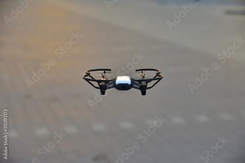 Valokuva Mały dron na niskiej wysokości na tle parkingu przed sklepem.
