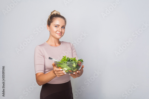 Valokuvatapetti Portrait of cheerful fit woman with hair bun holding bawl of green vegetable salad and looking at camera, vegetarian diet, healthy food, empty copy space for advertising