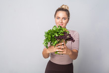Young Positive Girl Giving Bunch Of Fresh Cooking Herbs To Camera And Smiling, Leafy Green Vegetables, Holding Parsley Sorrel Lettuce, Healthy Nutrition, Organic Food. Studio Shot, Grey Background