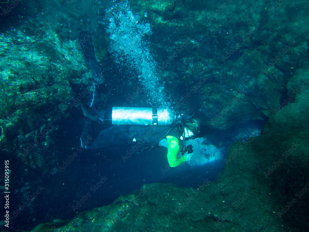 Fototapeta Underwater view of female scuba diver diving into cave.