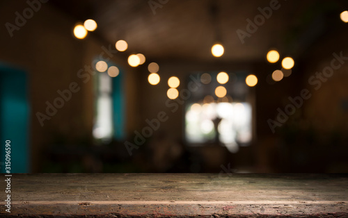 Empty wood table top on blur light gold bokeh of cafe restaurant in dark backgro Wallpaper Mural