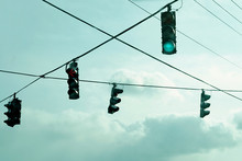 Traffic Lights Hanging On Wires In The Air.