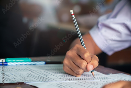 Fotografía  Hand of Student doing test or exam  in classroom of school with stress